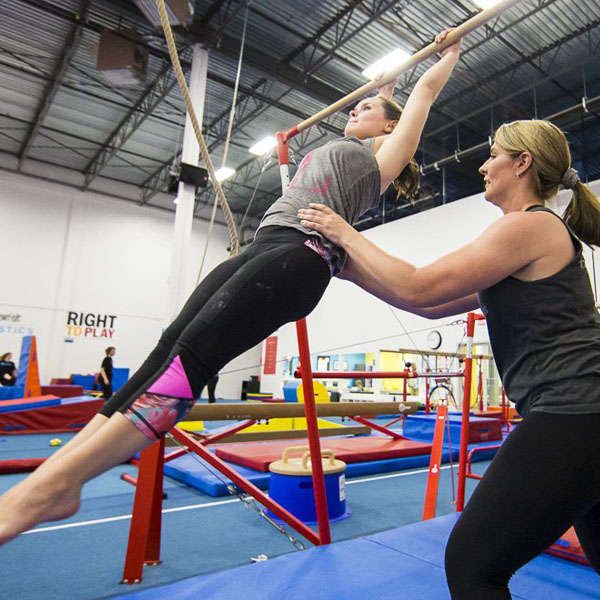 coach assiting an adult with shape while swinging on a bar