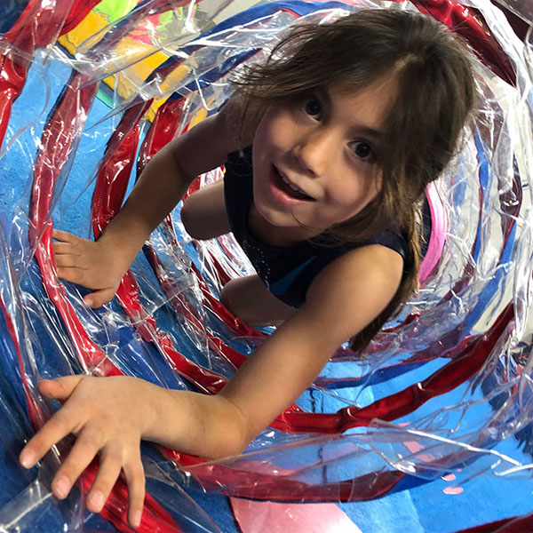 Girl crawling through plastic tunnel