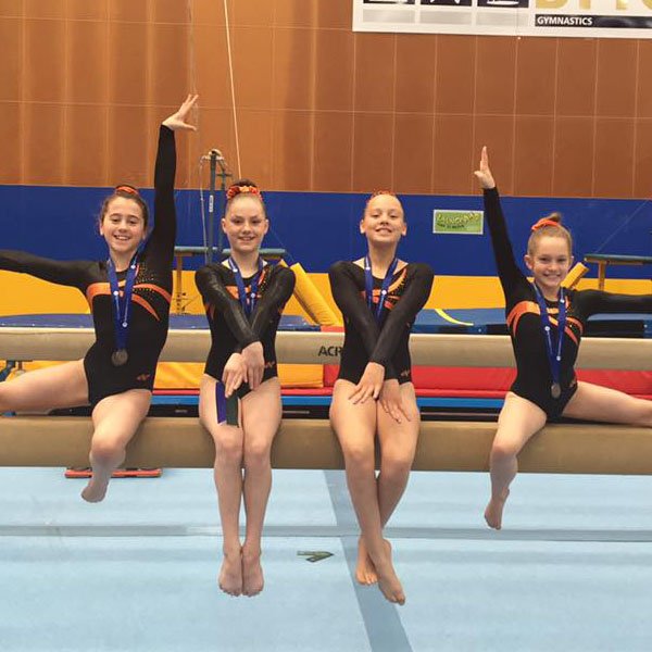 4 competitive gymnasts posing on a balance beam