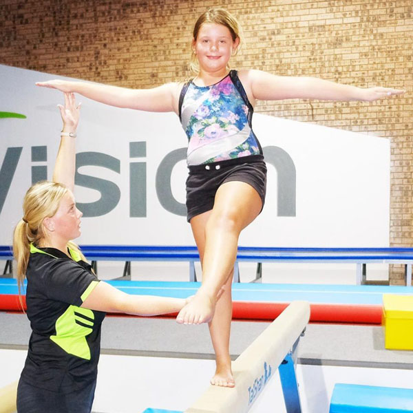 coach assisting and correcting a young gymnast on balance beam